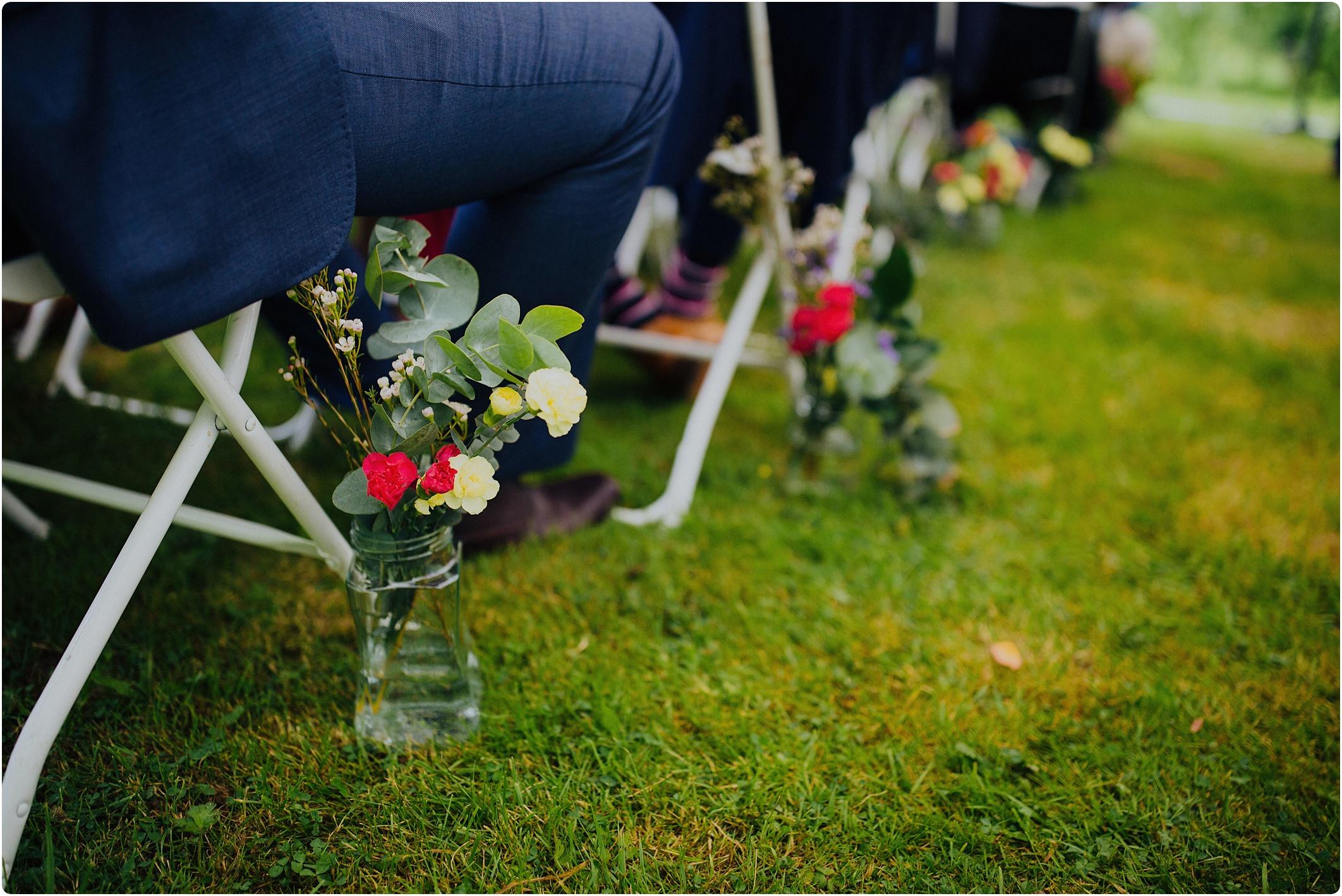 masonry jar with flowers down the aisle