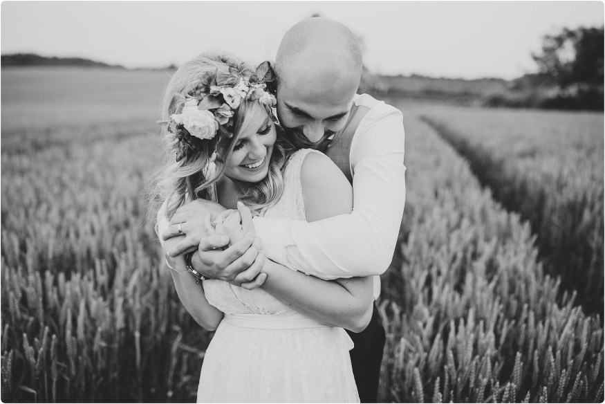 groom hugging bride in field at a cripps barn wedding