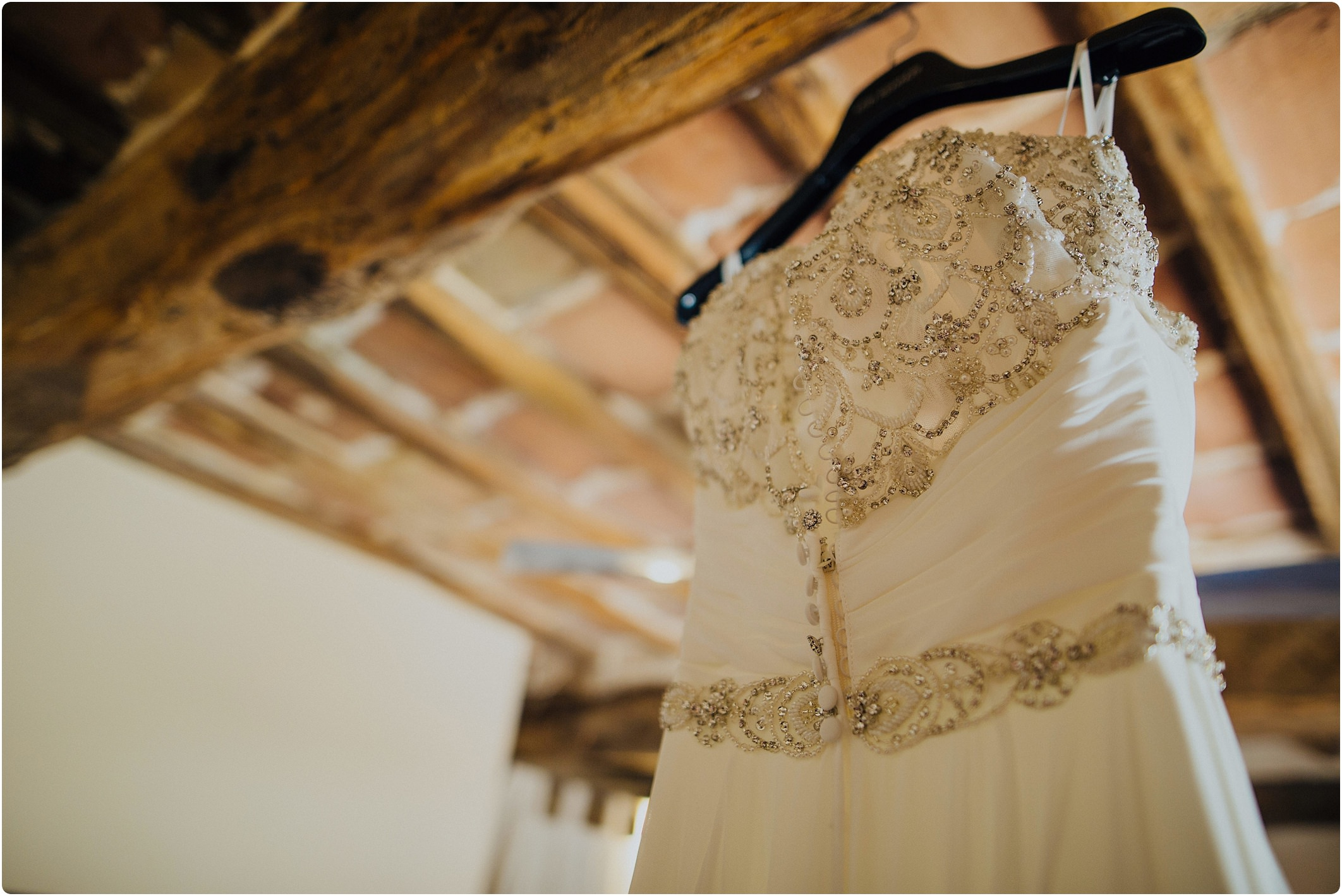 justin alexander dress with lace and sequin back hanging up at a tuscan wedding
