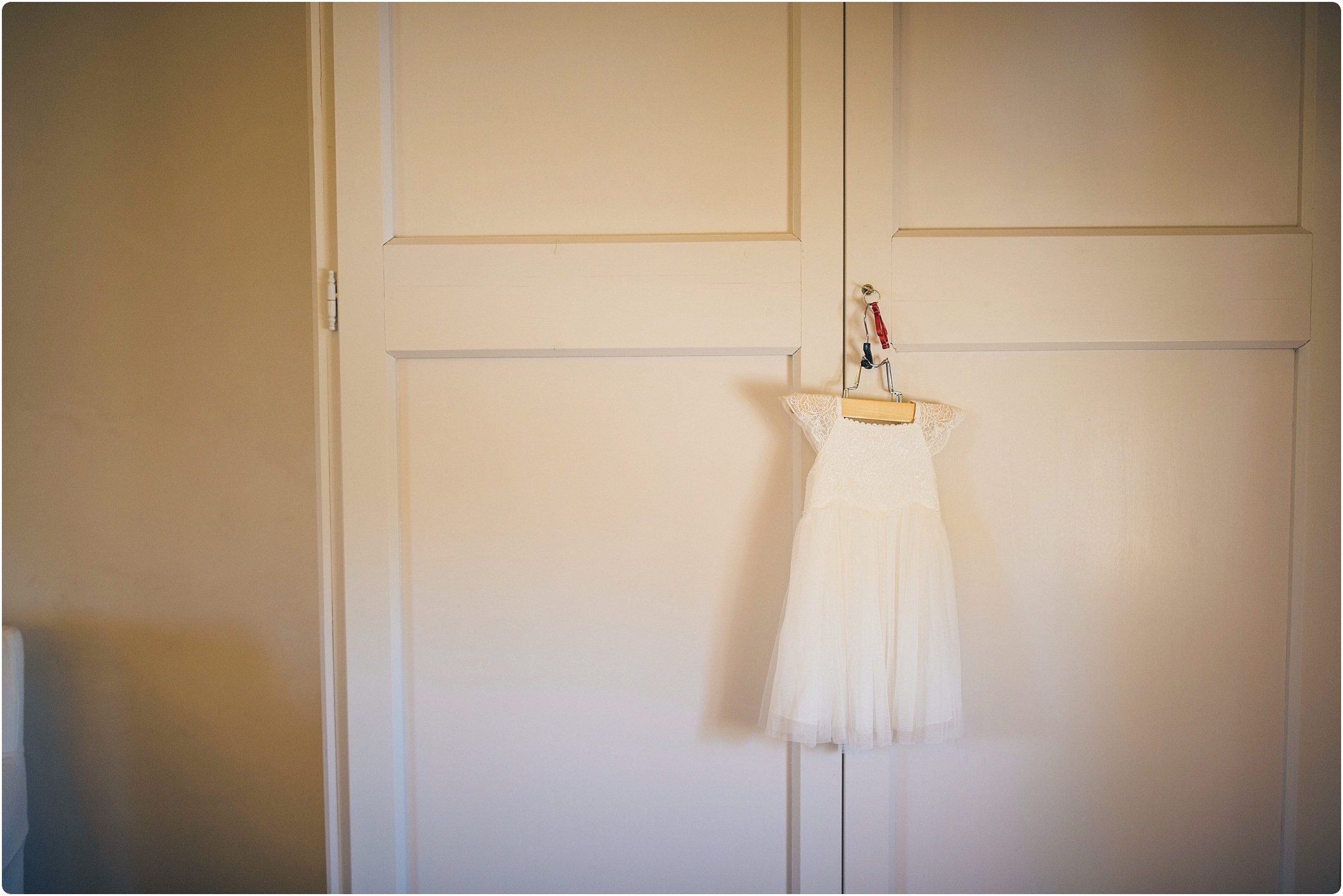 flower girl dress hanging up at a villa podernovo wedding