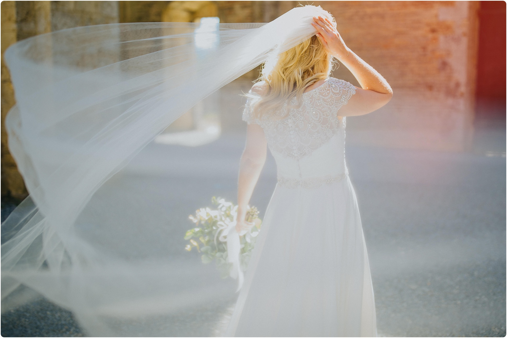 bride with veil caught in wind at a san galgano abbey wedding