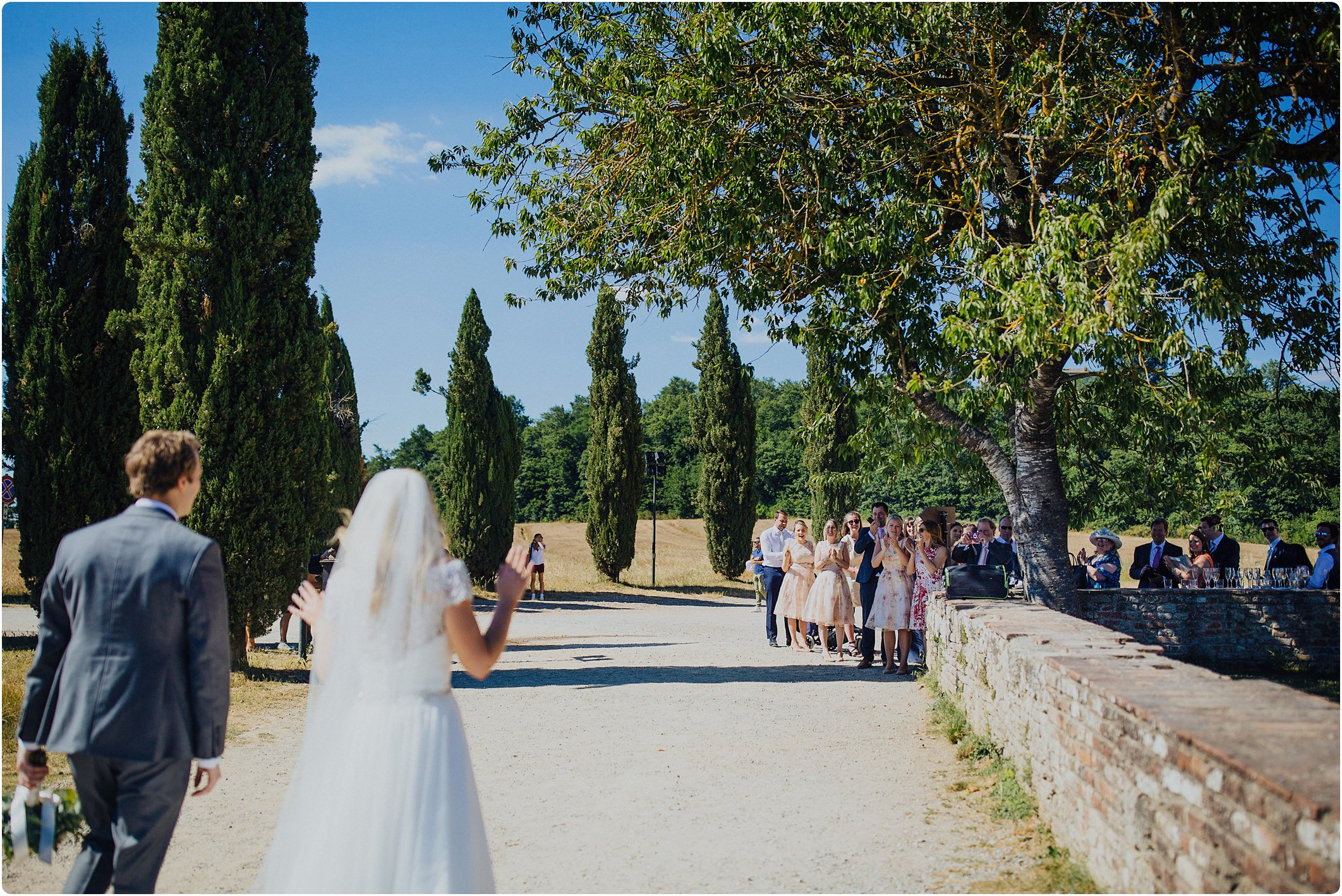 bride and groom walking back to guests outside a san galgano abbey wedding