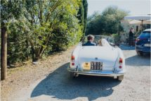 groom driving vintage alfa romeo at a villa podernovo wedding