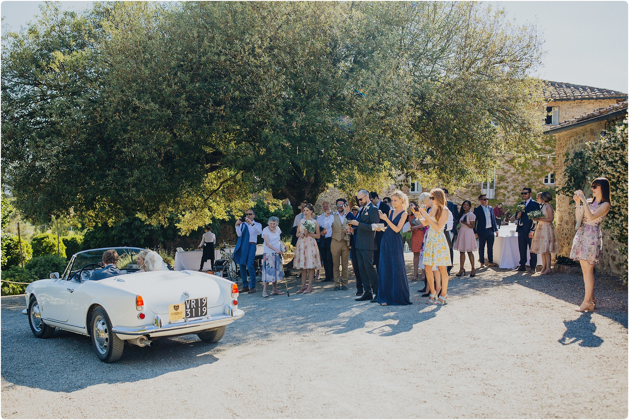 bride and groom just arriving in a vintage alfa romeo at a villa podernovo wedding