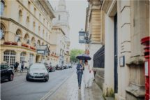 bride and groom walking with umbrella in Bristol]]