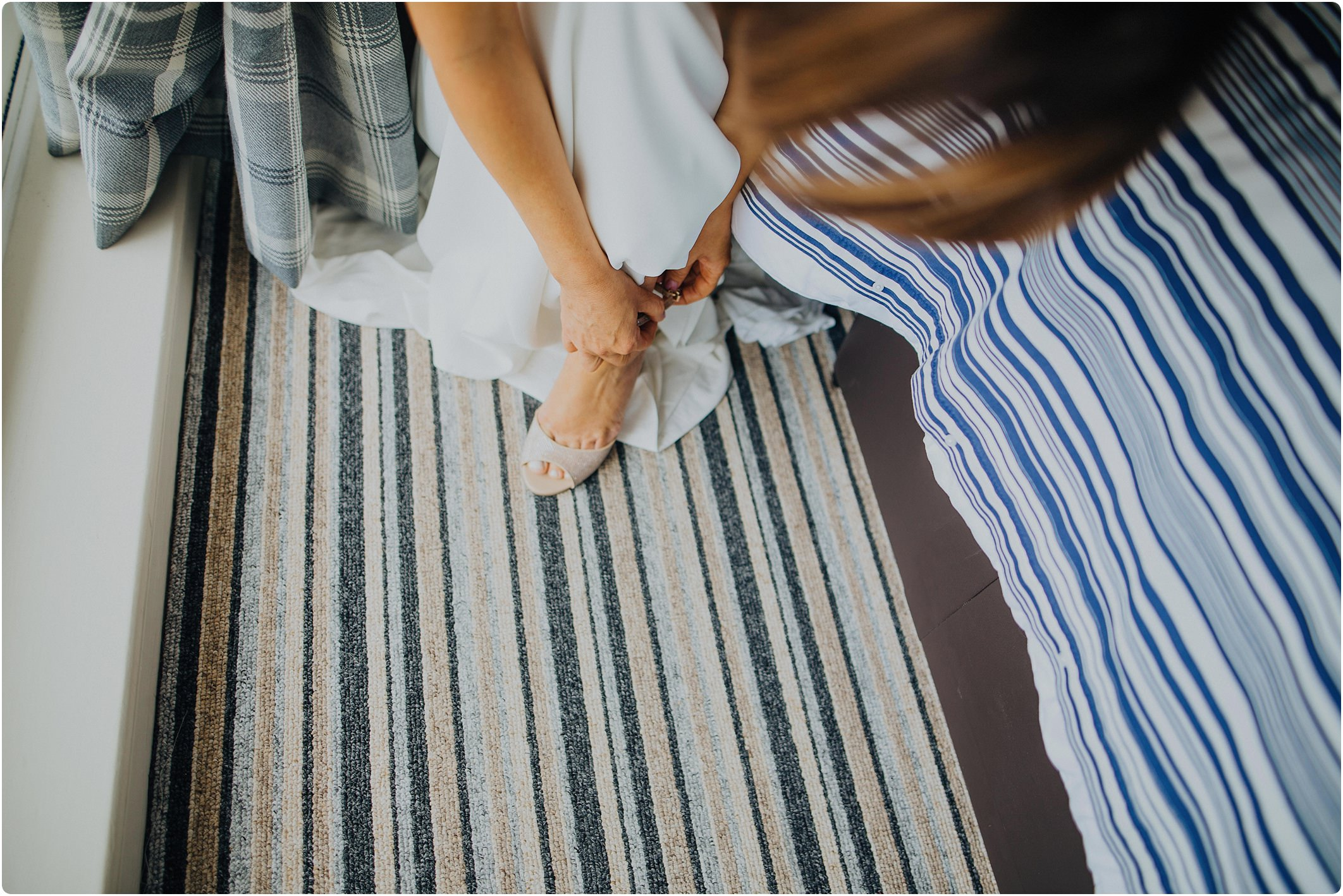 bride putting on shoes with a blue ribbon at woolacombe bay apartments