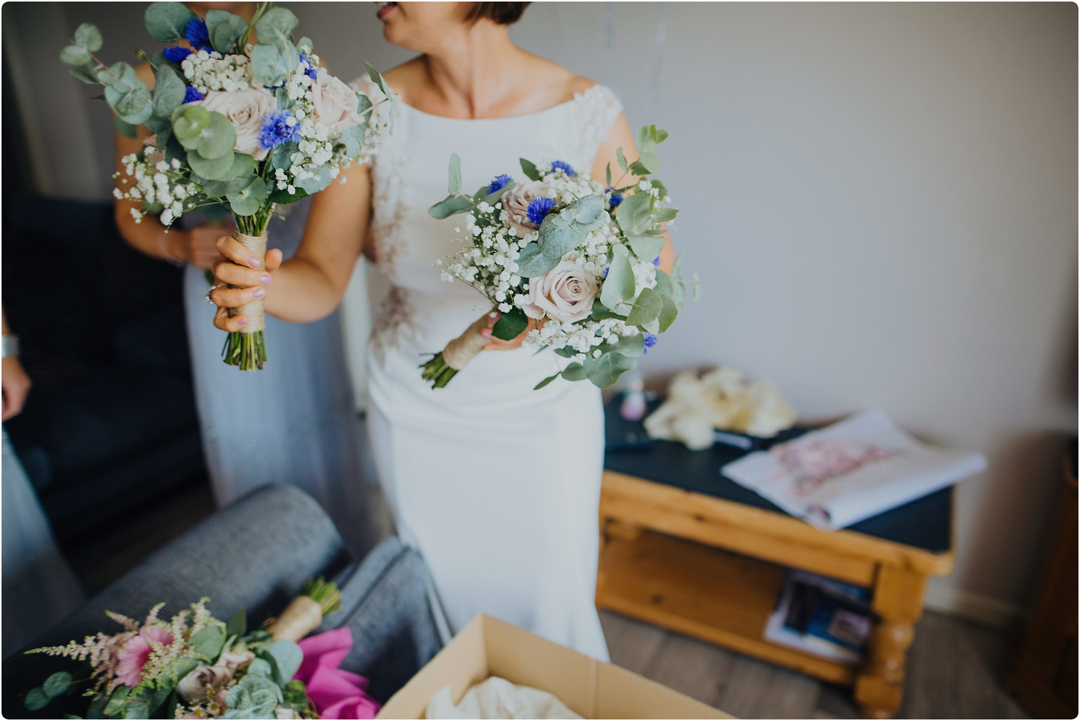 bride holding bouquets by off shore blooms