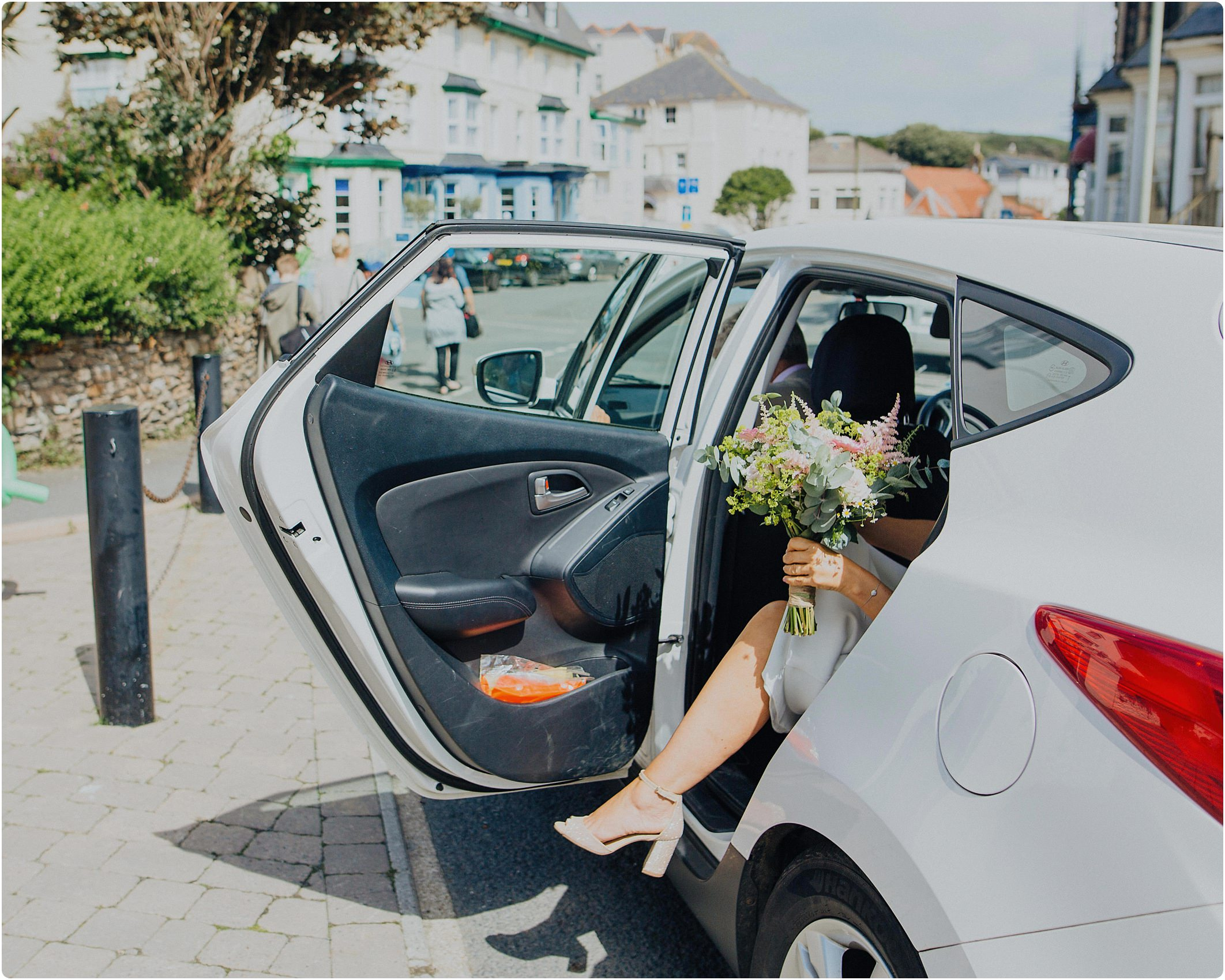 bride getting out of car for a tunnels beach wedding