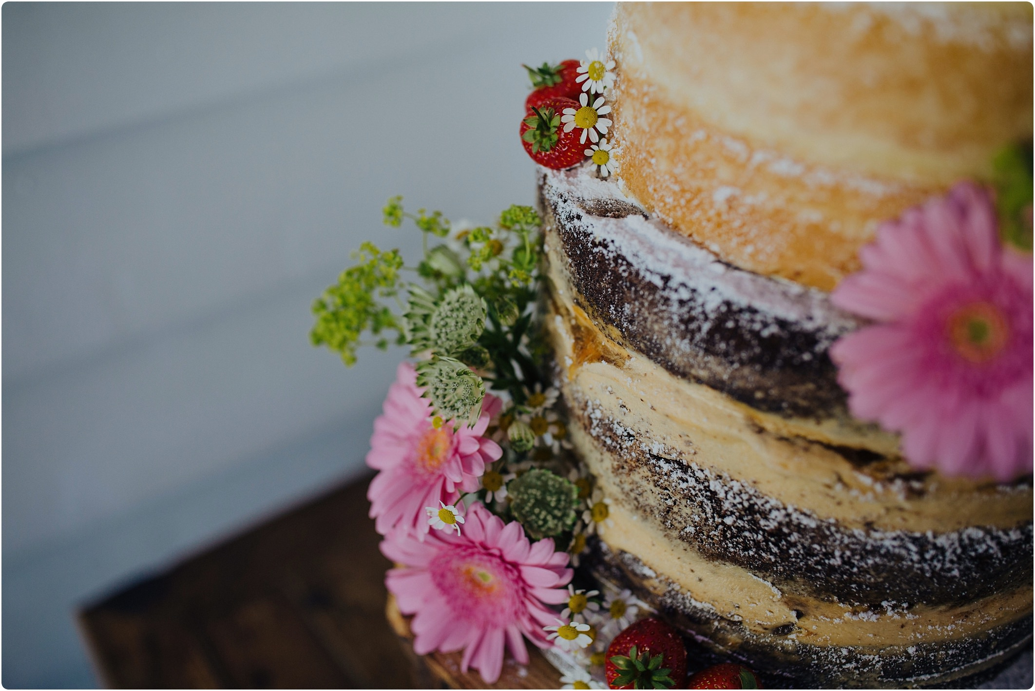 naked cake decorated with flowers by Liz Jones at a tunnels beach wedding