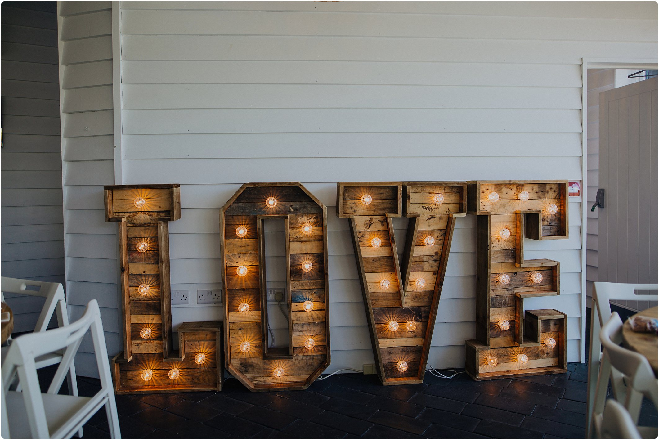 love lights made from pallets at a tunnels beach wedding