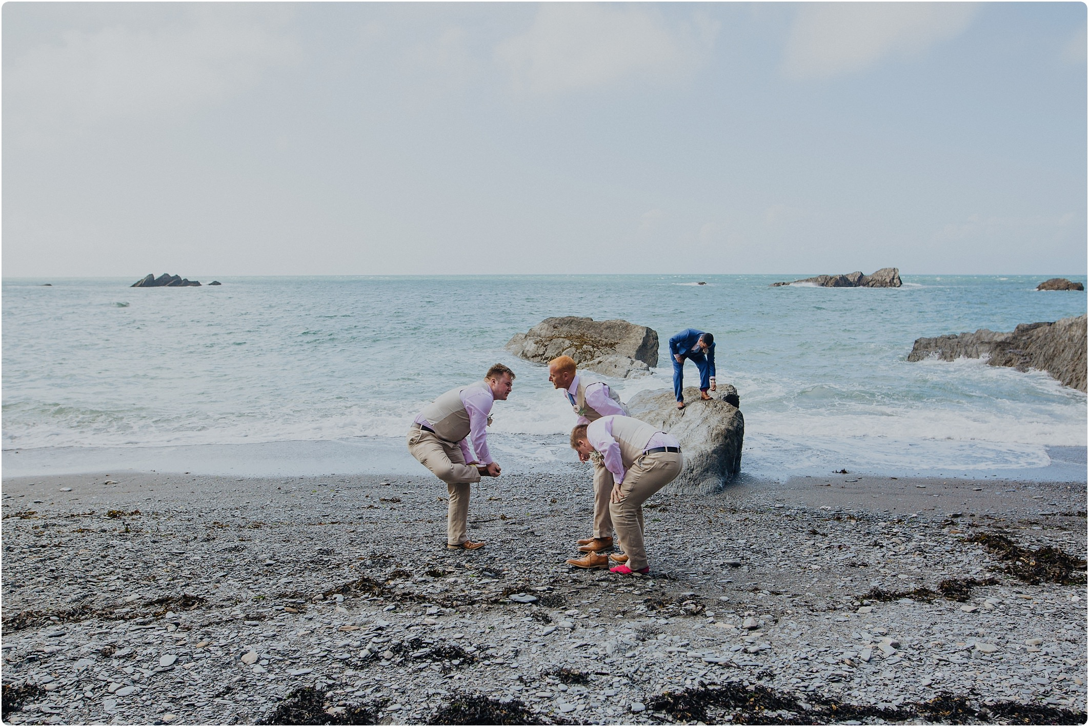 groomsmen taking their shoes off at a tunnels beach wedding