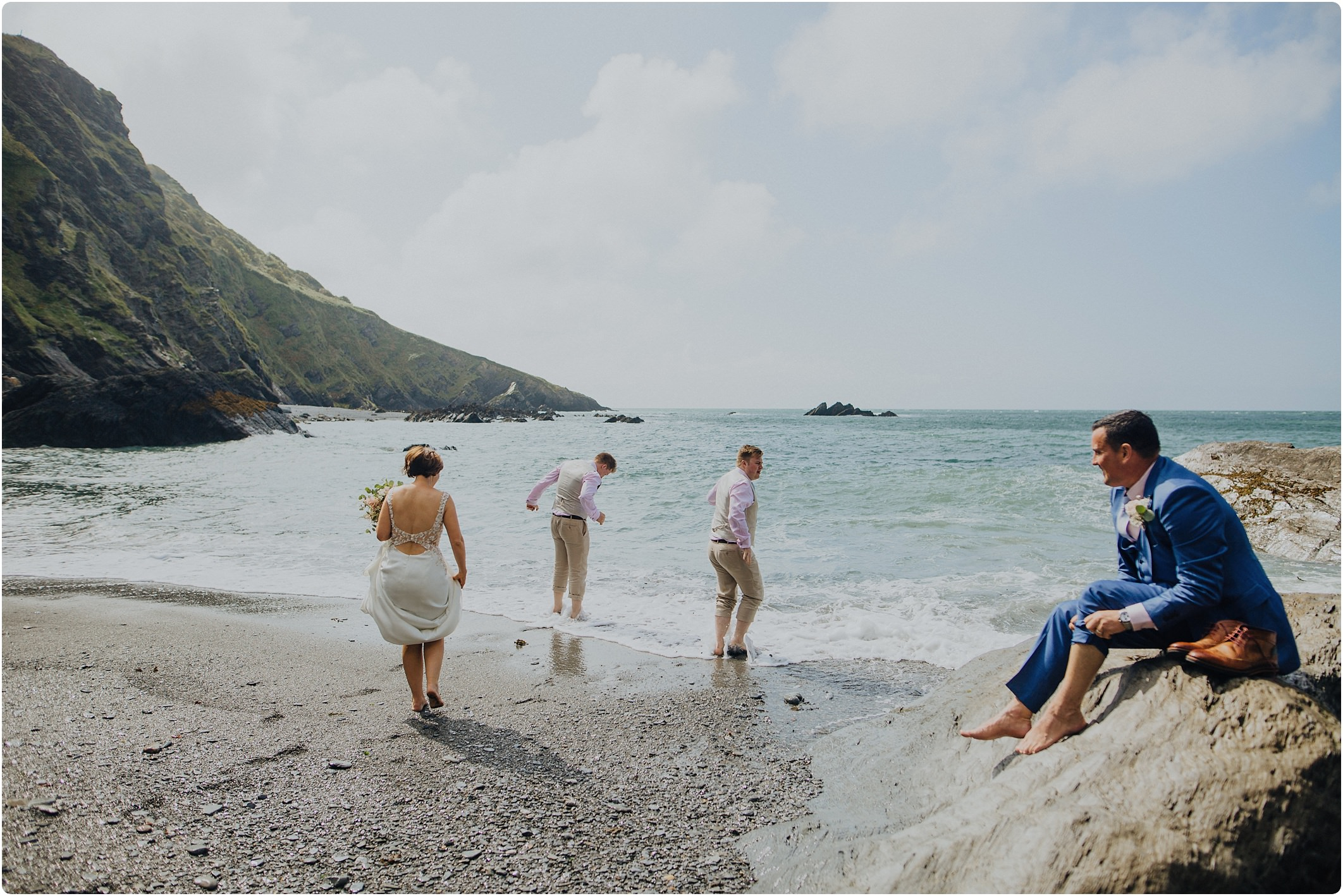 bridal party going into the sea at a tunnels beach wedding