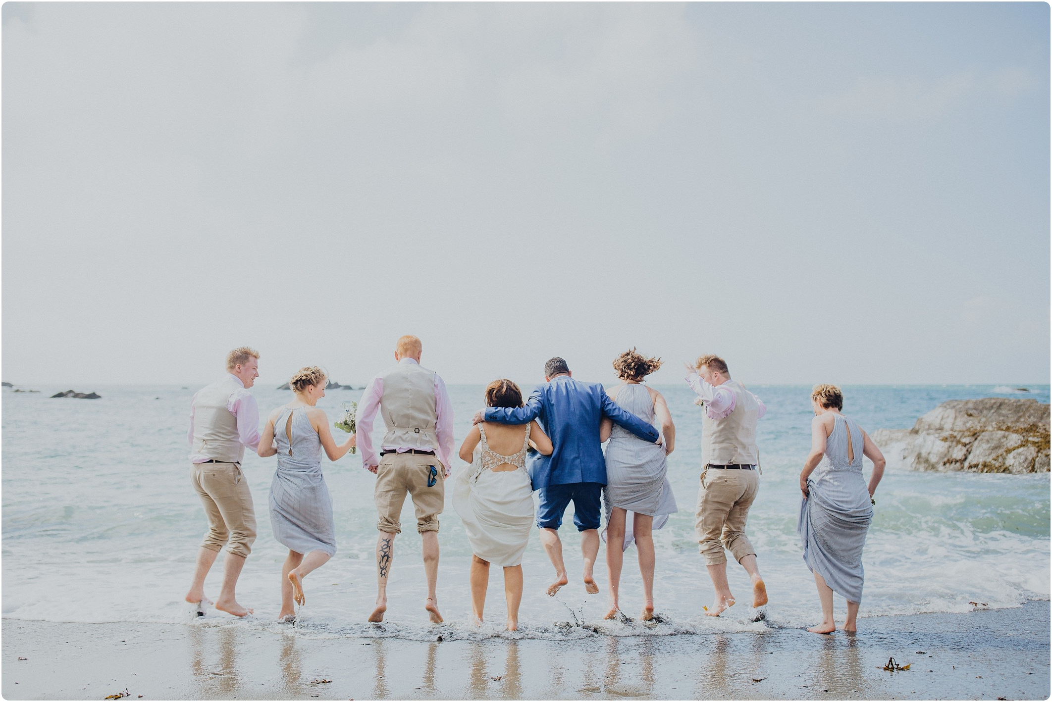 bridal party in the sea at a tunnels beach wedding