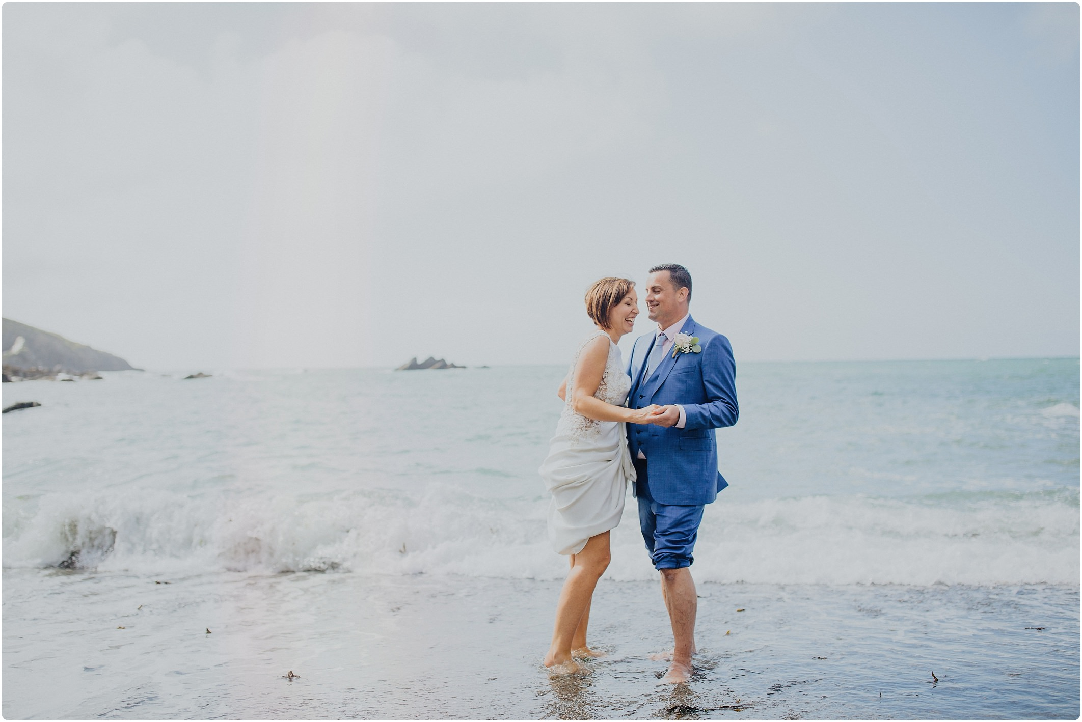 bride and groom in sea at a tunnels beach wedding