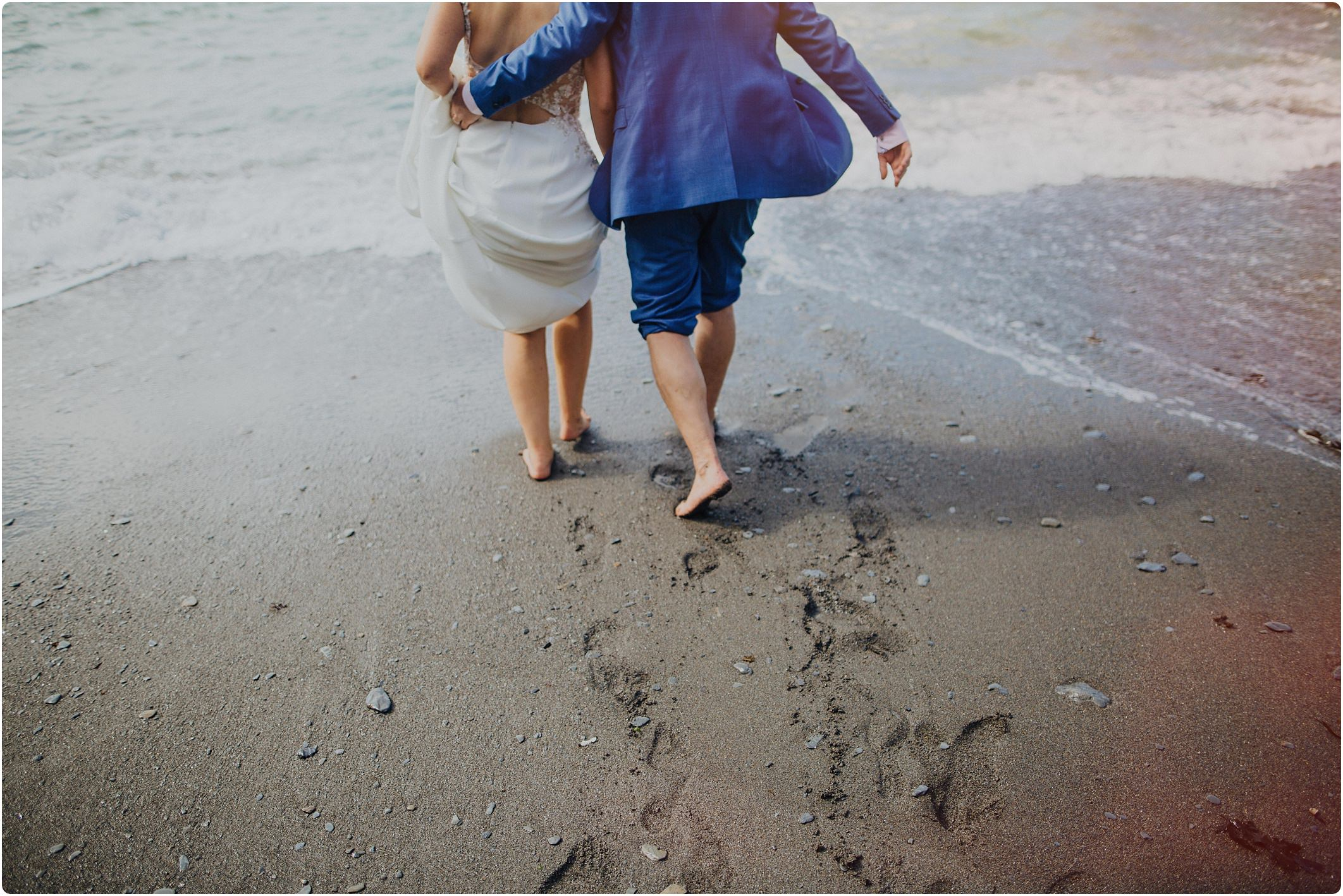 bride and groom walking in the sand at a tunnels beach wedding