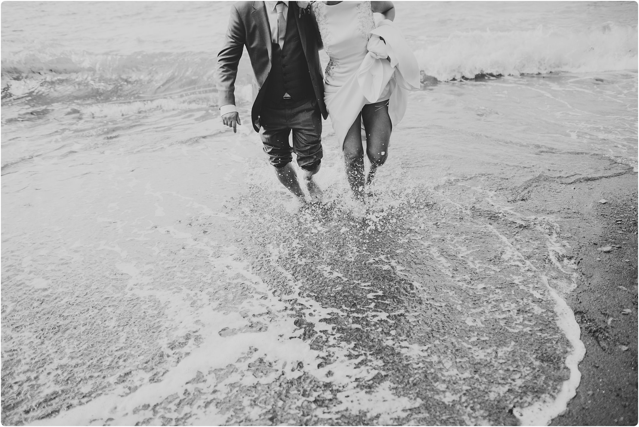 bride and groom running in the sea at a tunnels beach wedding