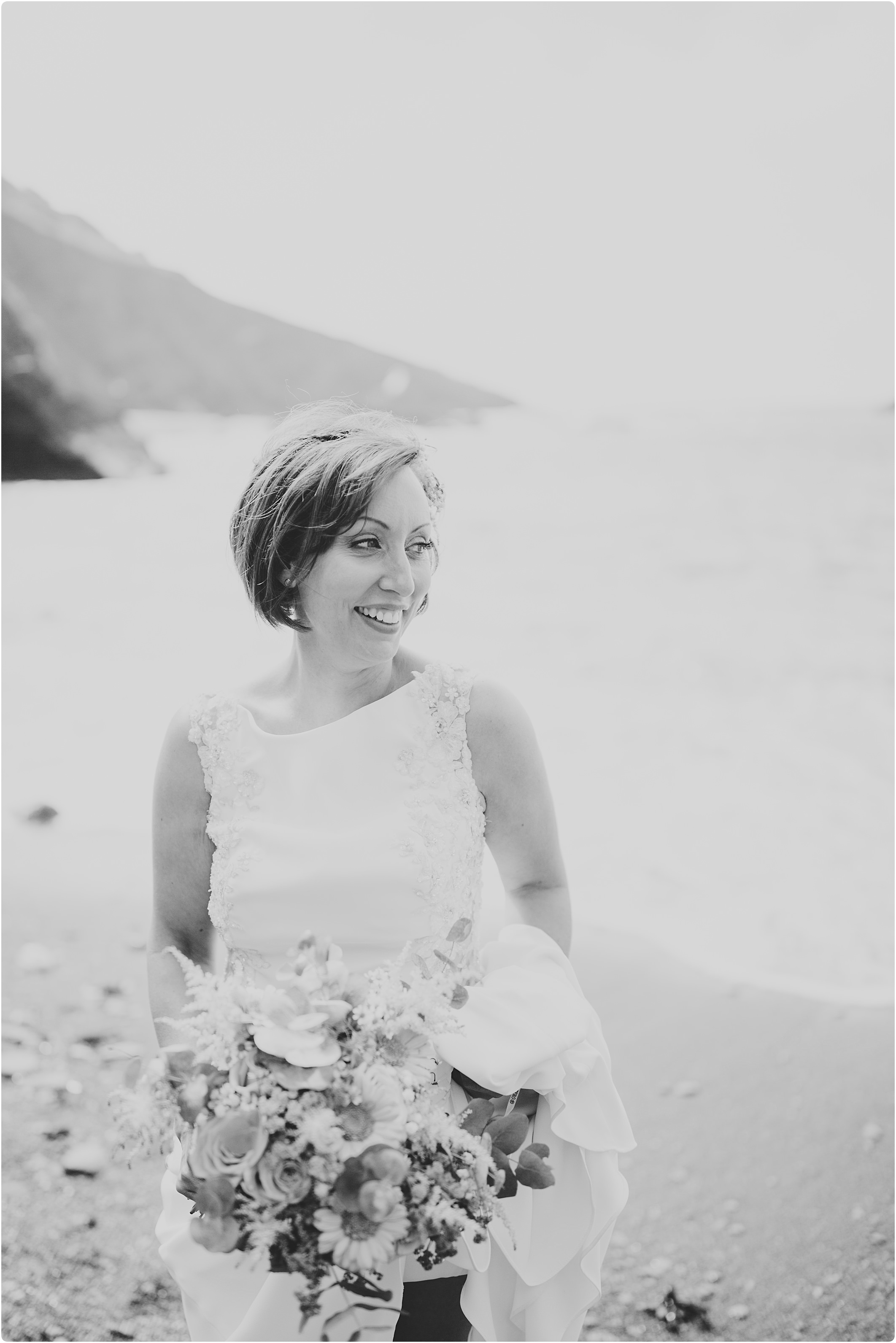 black and white of bride on beach at a tunnels beach wedding