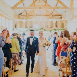 bride and groom walking down aisle at Kingscote Barn