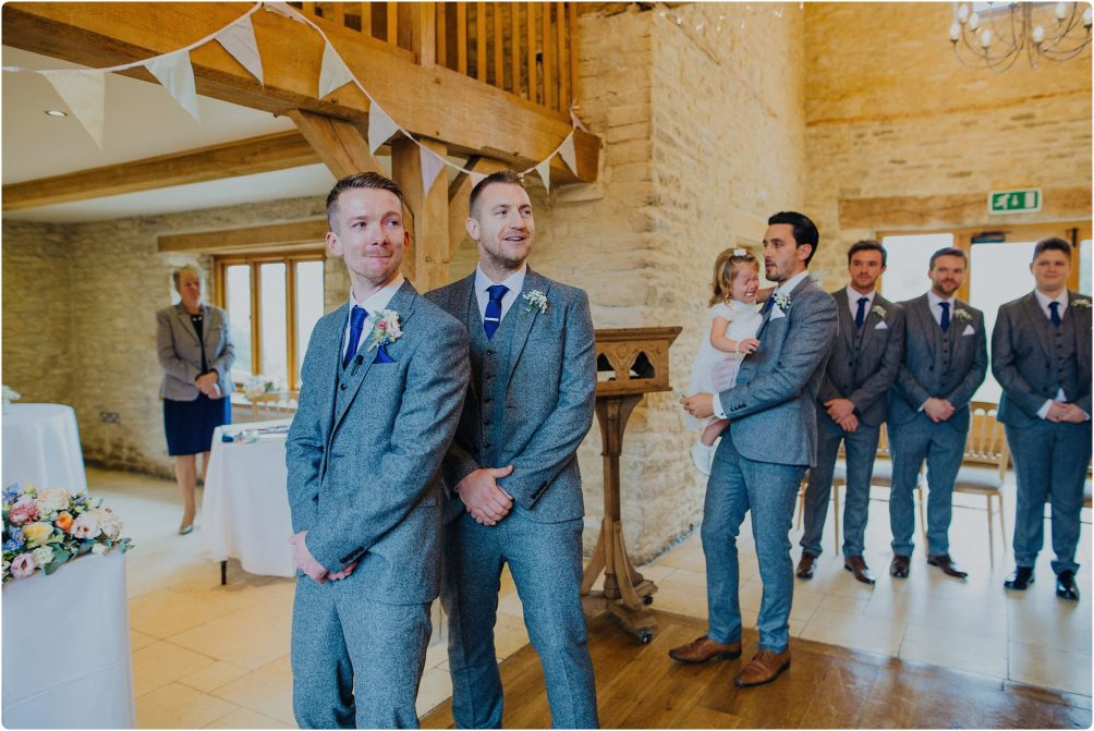 groom crying as he sees bride come down the aisle at Kingscote Barn