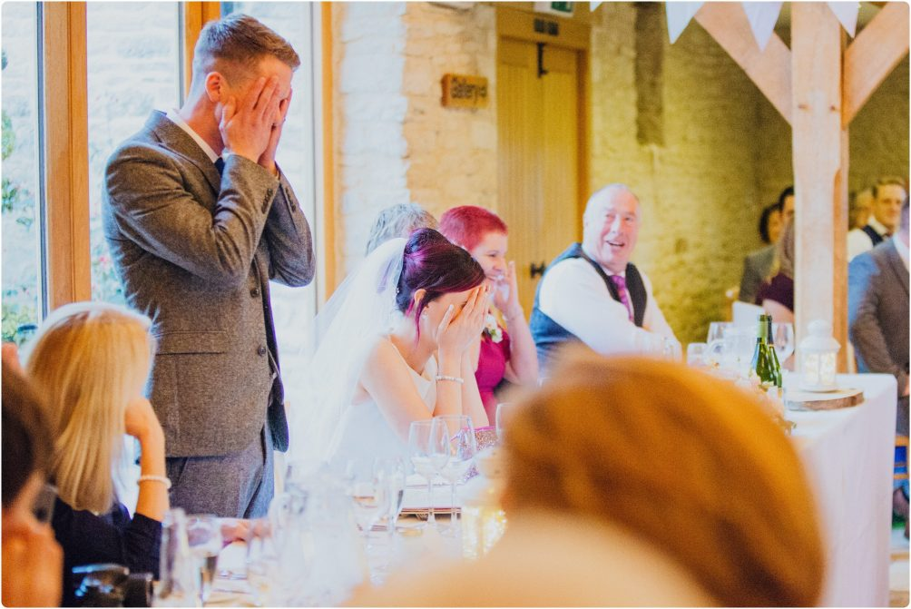 bride and groom with their hands over their faces during the grooms speech