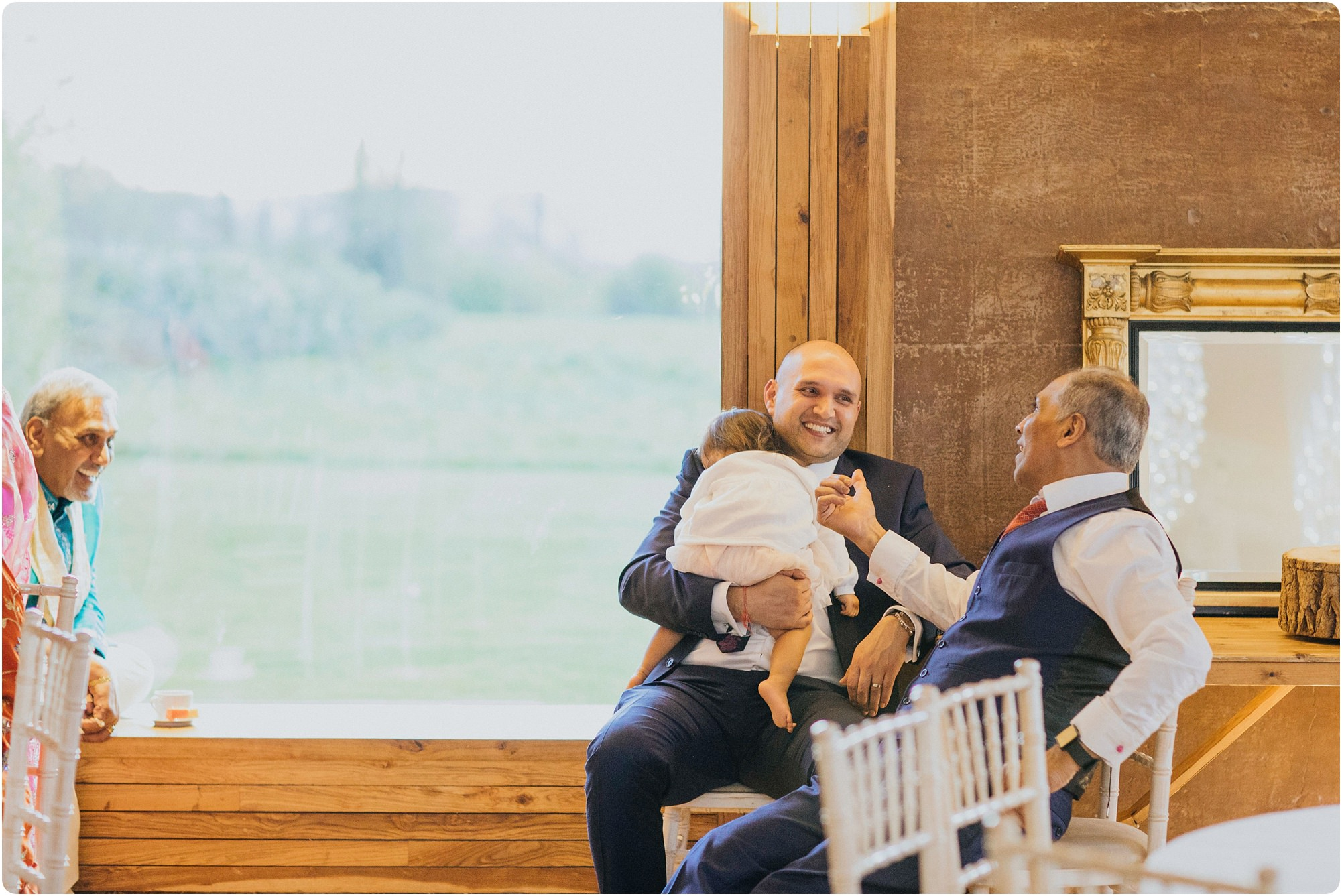 men chatting with baby at an Elmore Court Wedding