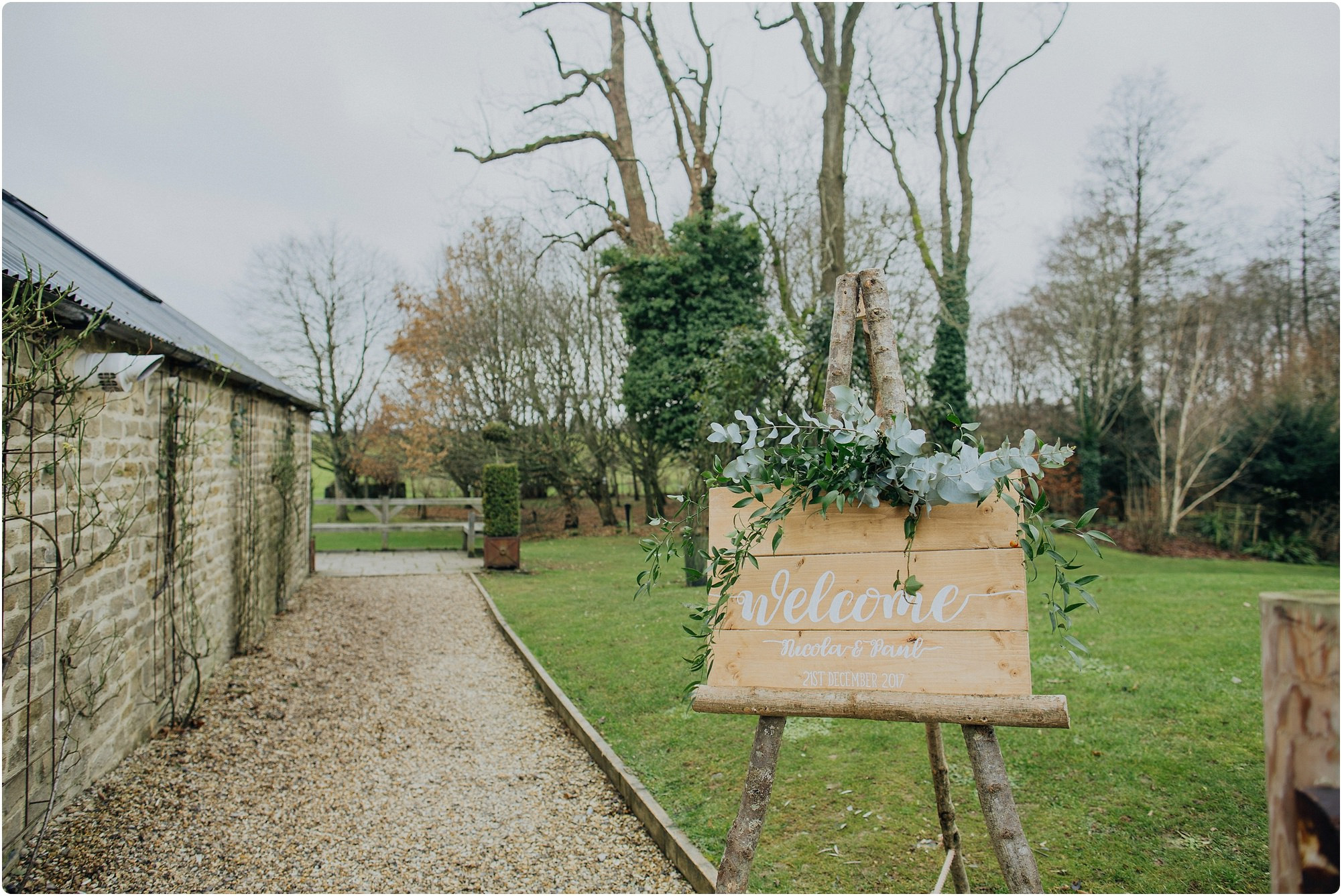 wooden welcome sign and flowers at a Cripps Barn wedding
