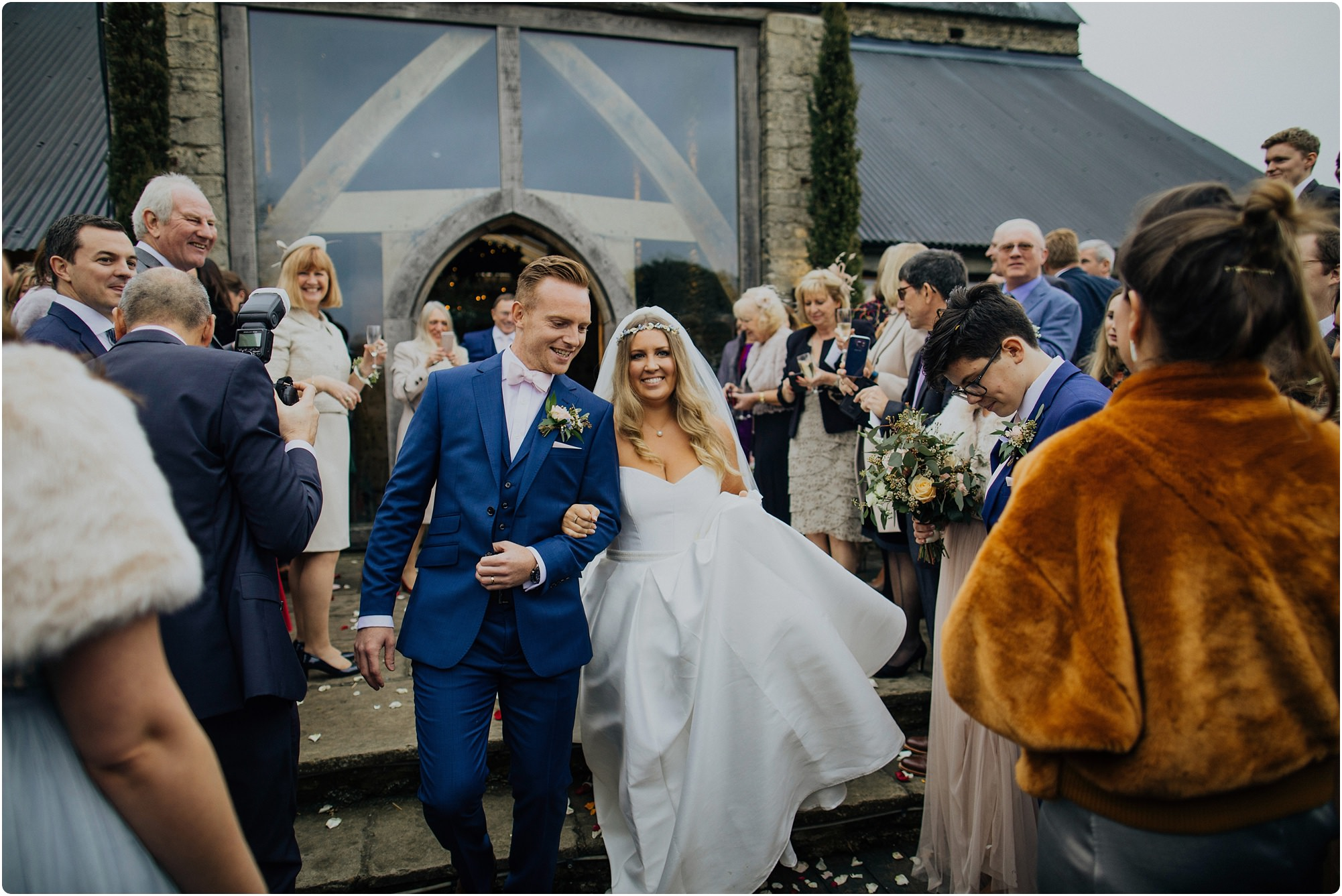 Bride and groom walking out to confetti at a Cripps Barn Winter Wedding