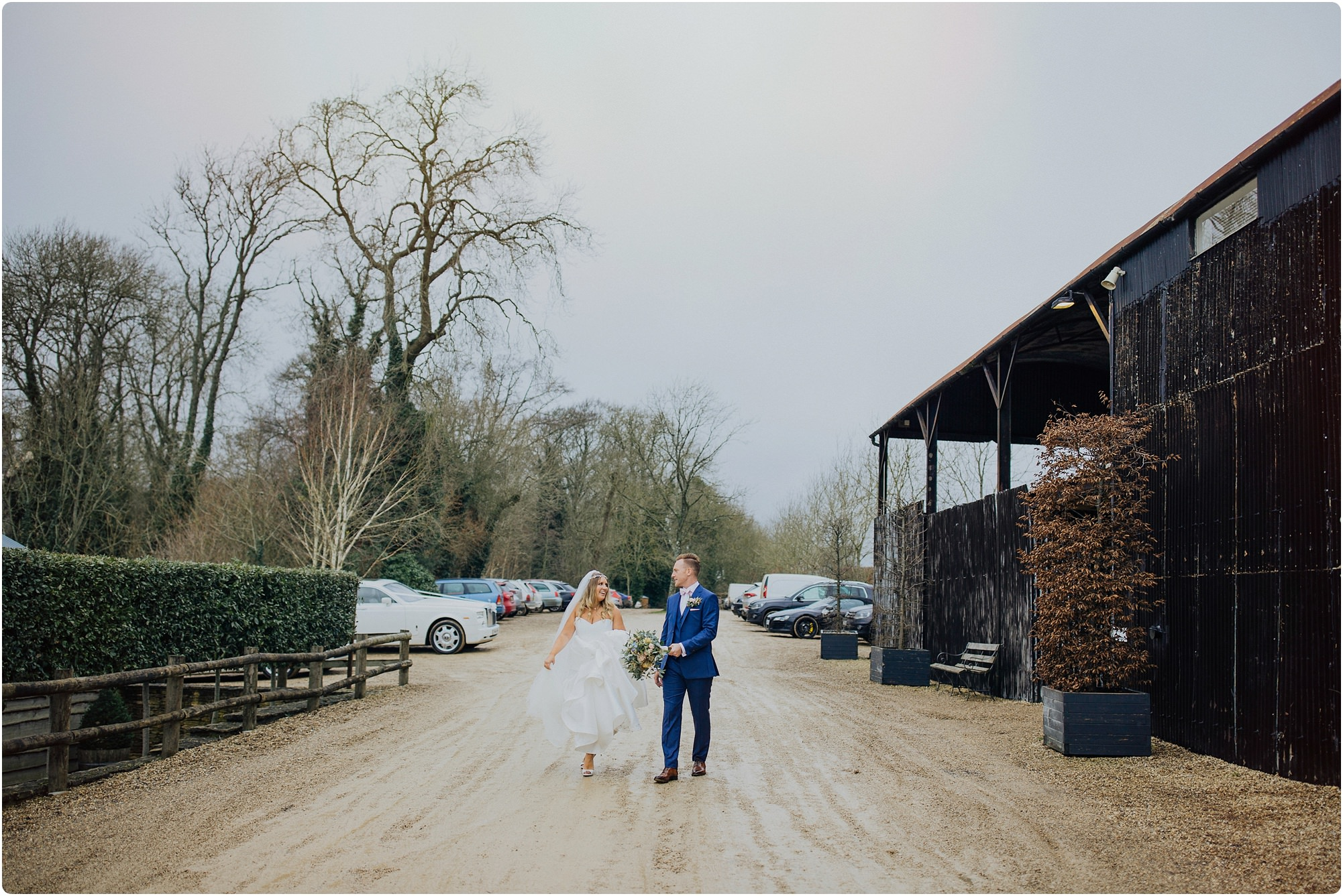 bride and groom walking down drive at a Cripps Barn Winter Wedding