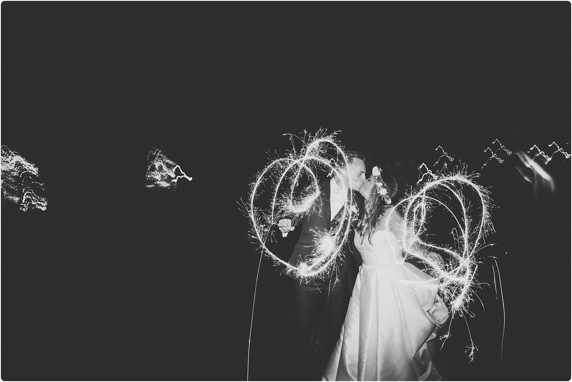bride and groom kissing whilst playing wth sparklers at a Cripps Barn Winter Wedding