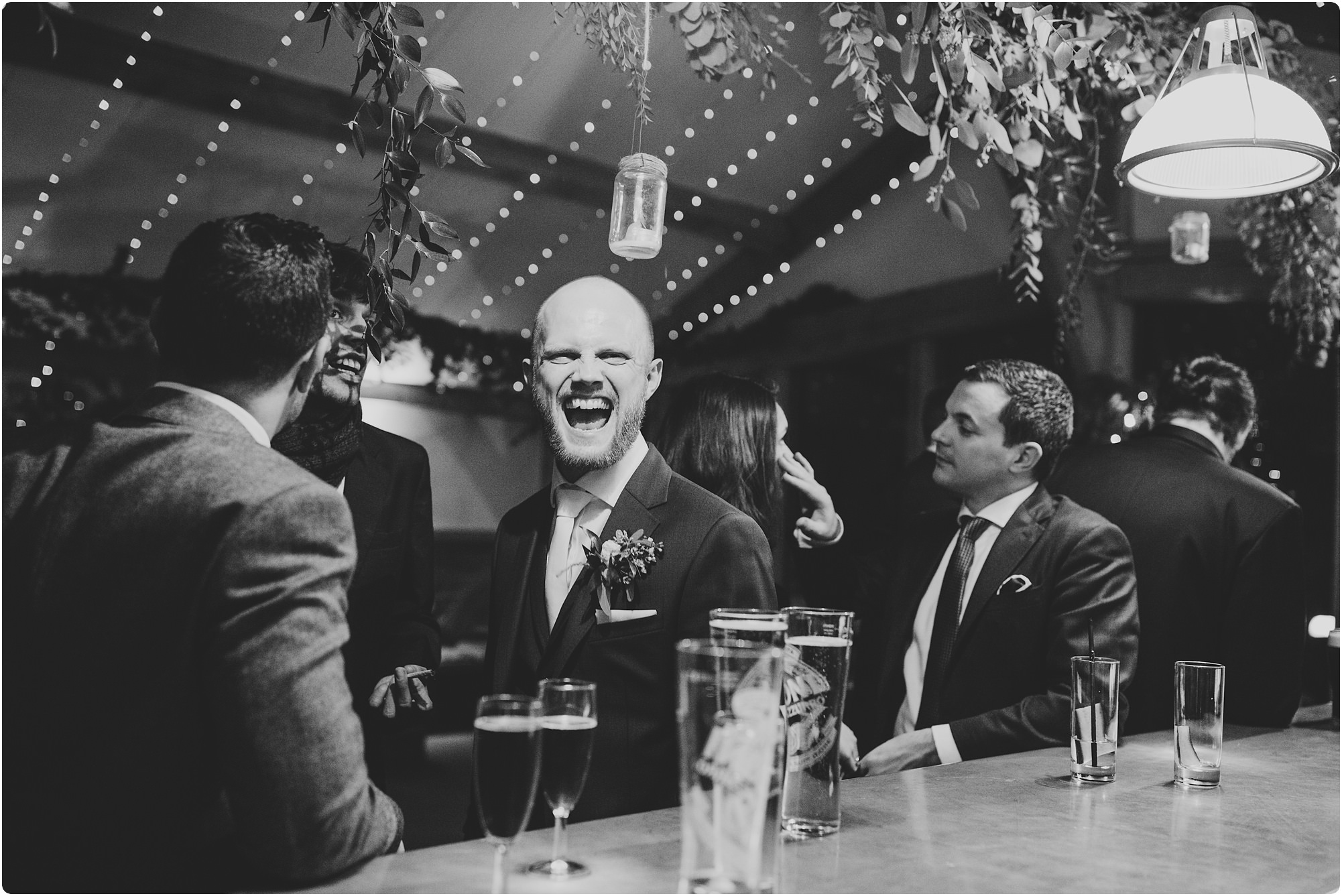 best man laughing at the bar at a Cripps Barn Winter Wedding