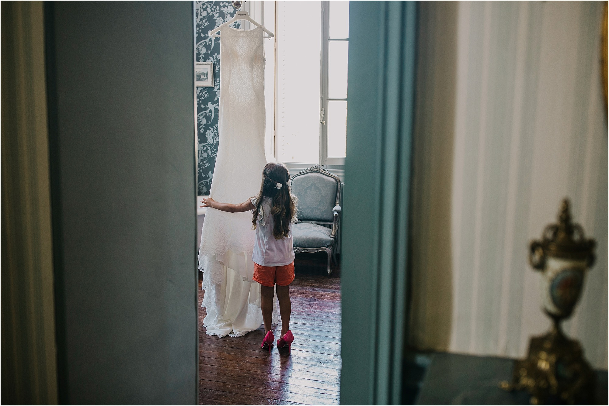 little girl looking at wedding dress hanging up at a chateau la durantie wedding