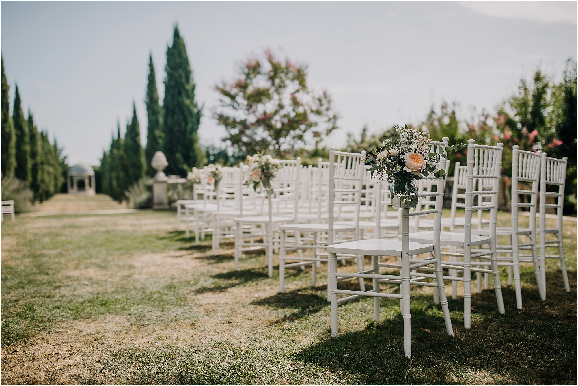 flowers on the chairs at an outdoor ceremony at chateau la durantie