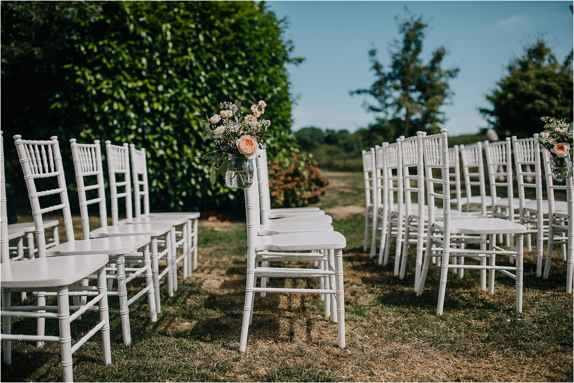 flowers in the vine chair decoration at an outdoor ceremony at chateau la durantie