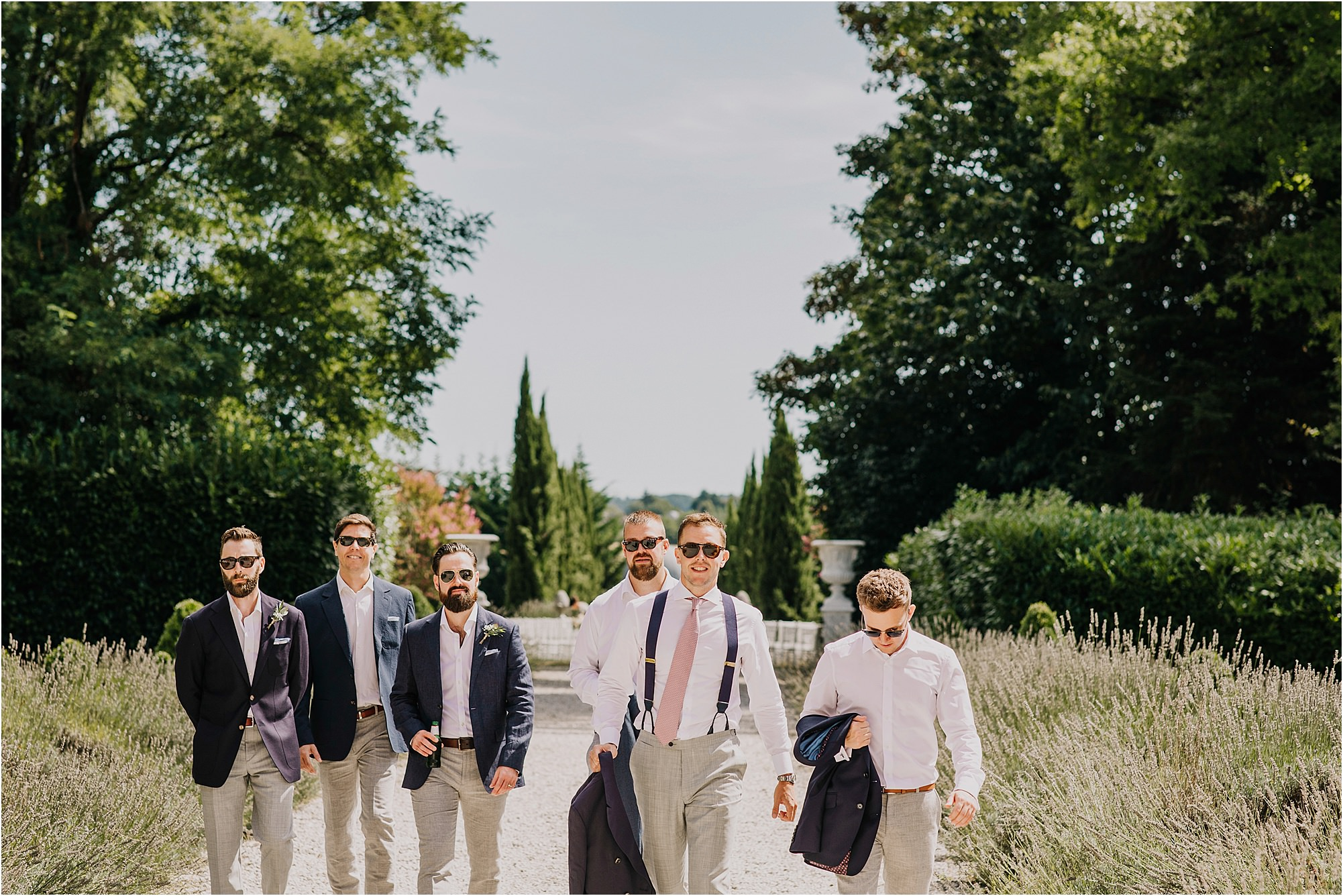 groomsmen and groom walking up the path at chateau la durantie