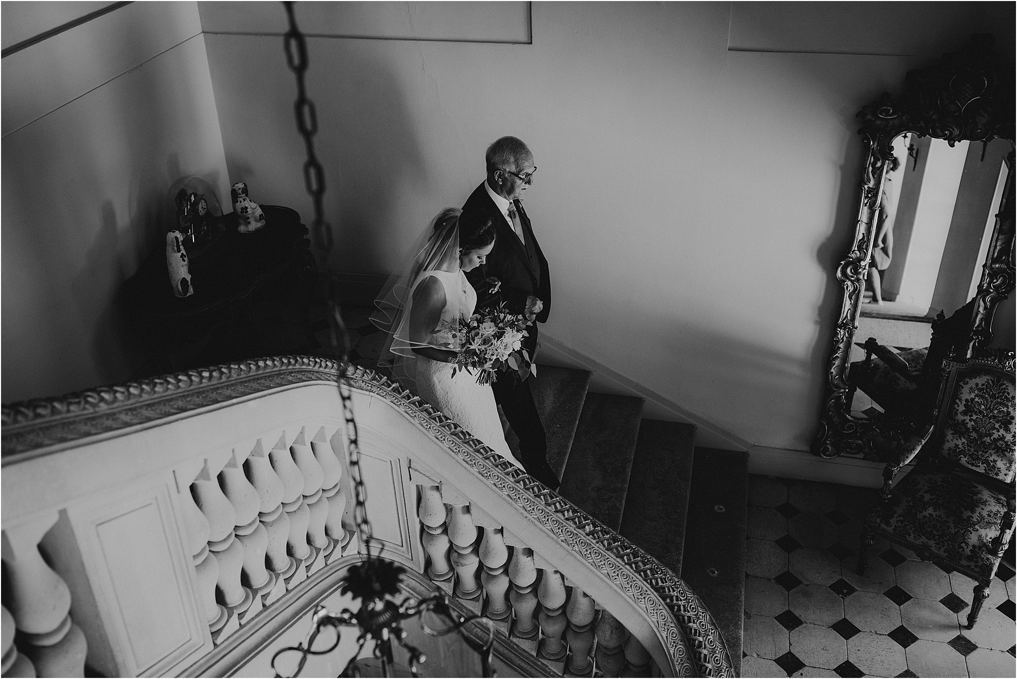black and white of bride and father walking down the stairs at achateau la durantie wedding