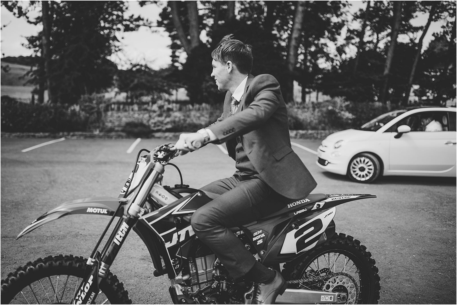groom arriving on motorcross bike at Kingscote Barn