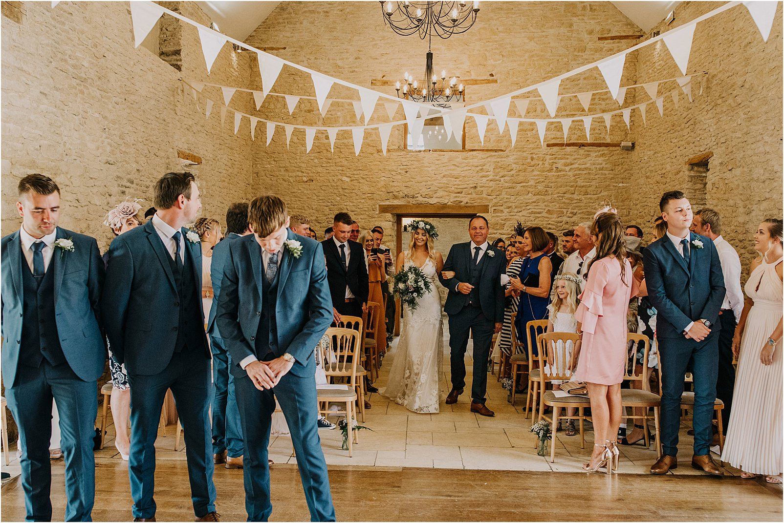 bride first walking in at Kingscote Barn ceremony