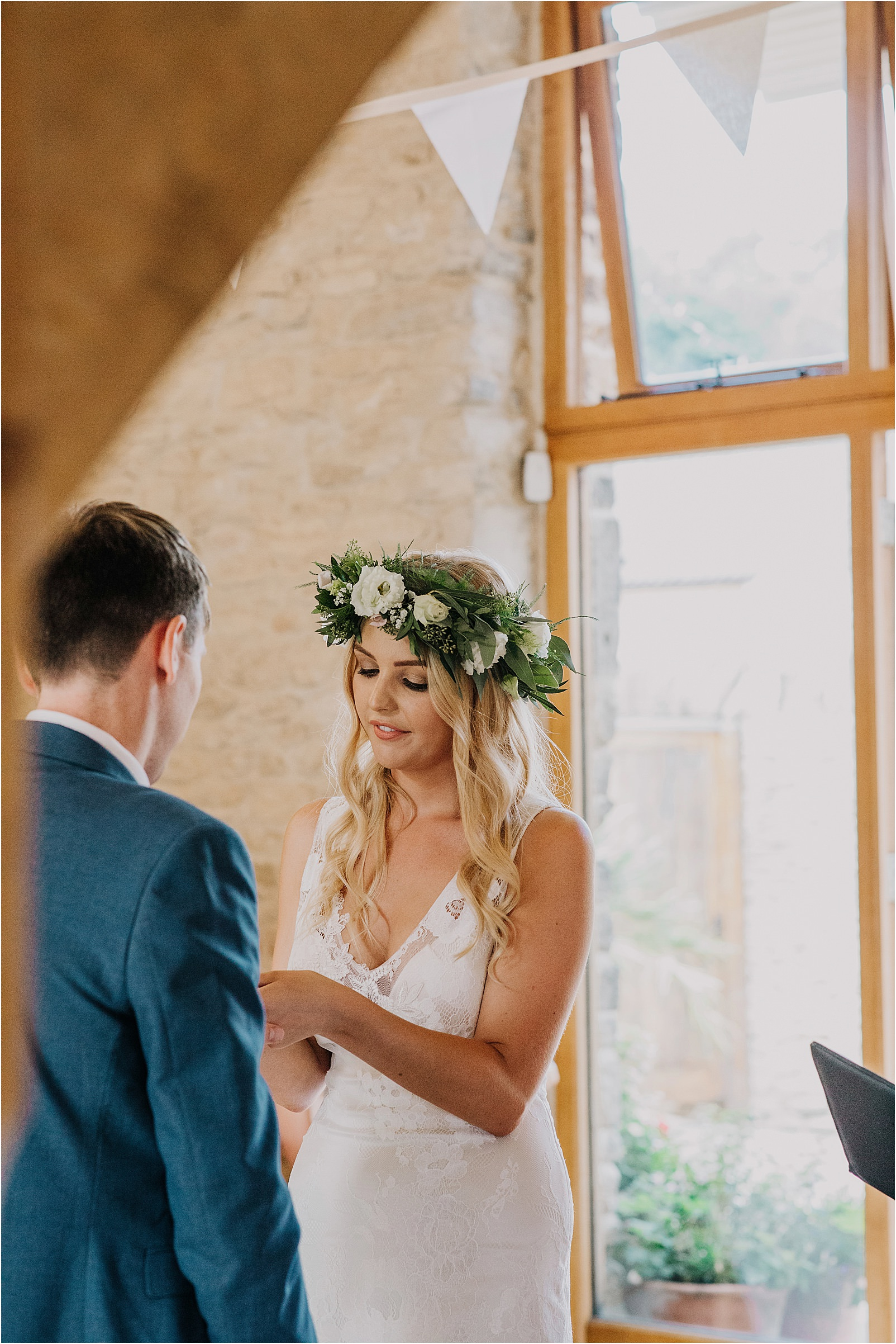 flower crown bride exchanging rings at Kingscote Barn wedding