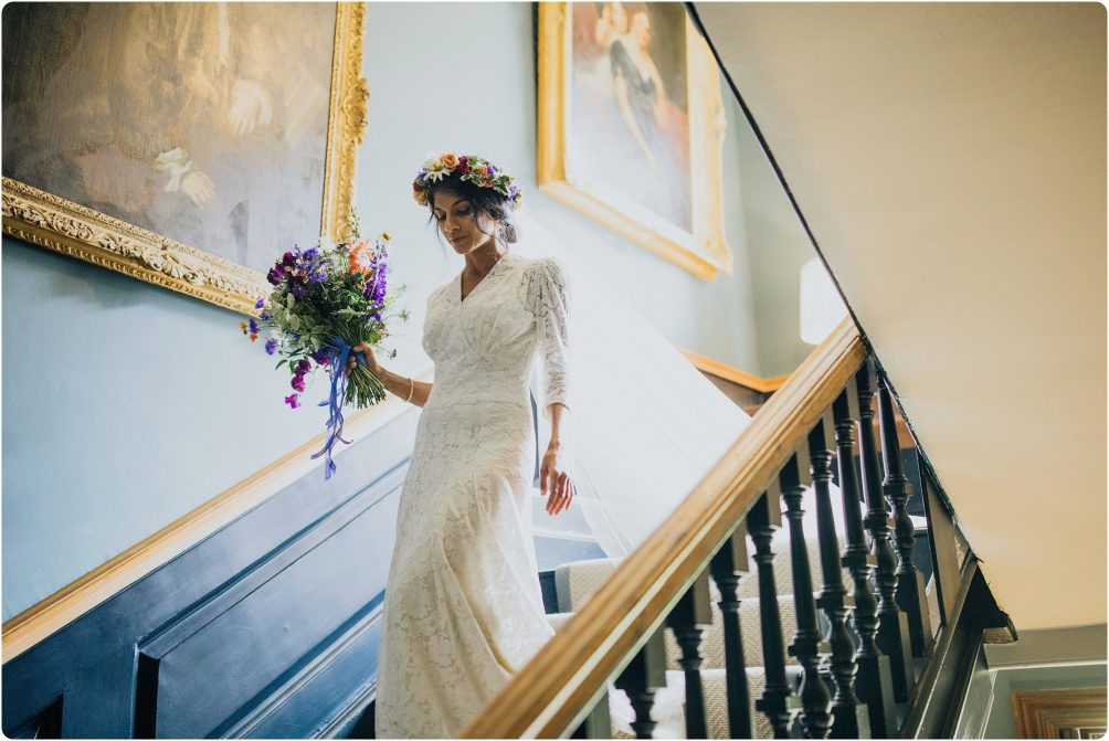 bride walking down the stairs at a Elmore Court wedding