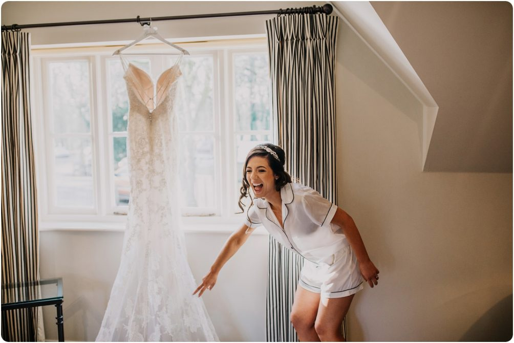 bride laughing by her enzoani dress at a kingscote barn wedding