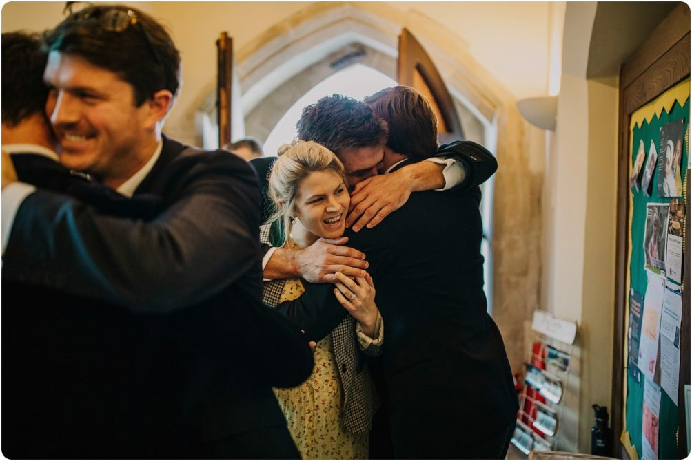 guests hugging the groom at church at a kingscote barn wedding