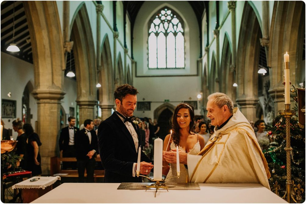 bride and groom lighting candle at woodchester priory