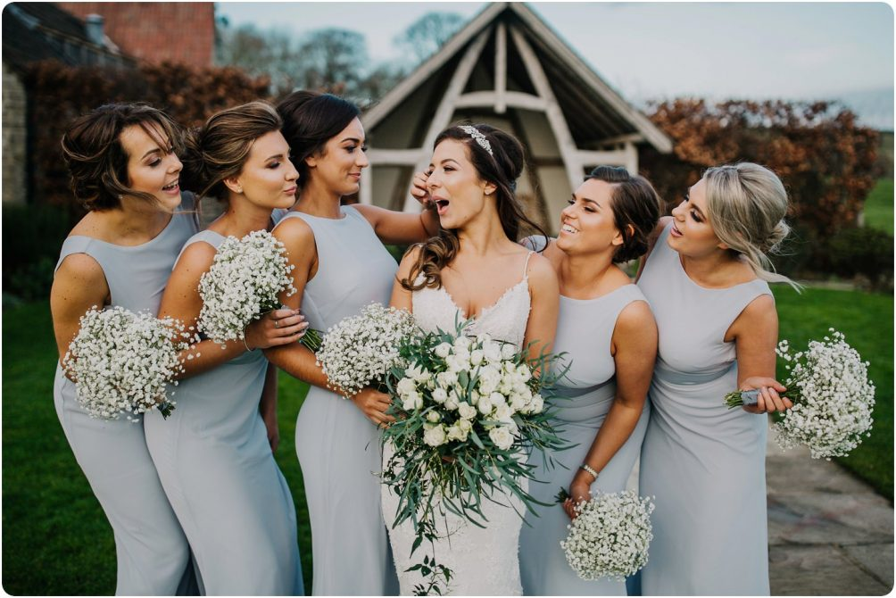 bride and bridesmaids in grey dresses at a kingscote barn wedding