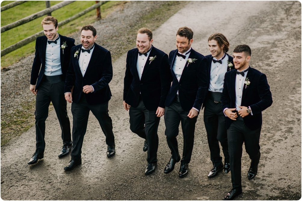 groom and groomsmen walking at a kingscote barn wedding
