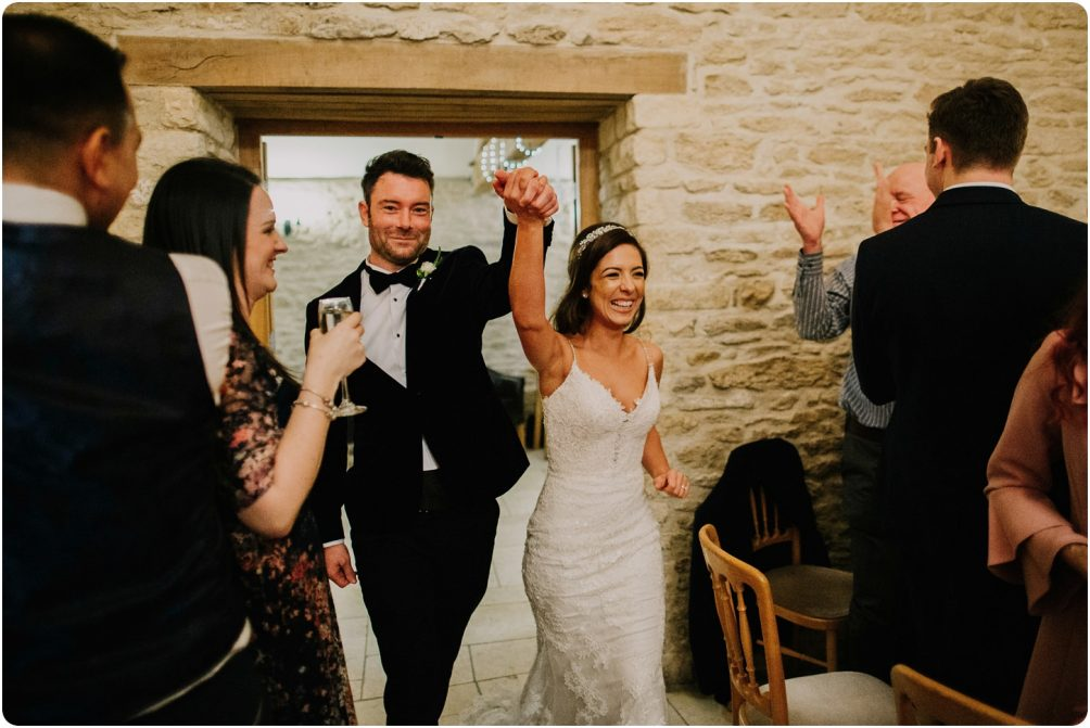 bride and groom walking into room a kingscote barn wedding