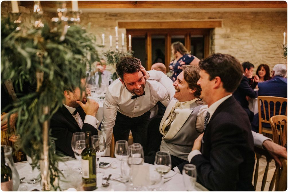 groom talking to guests at a kingscote barn wedding