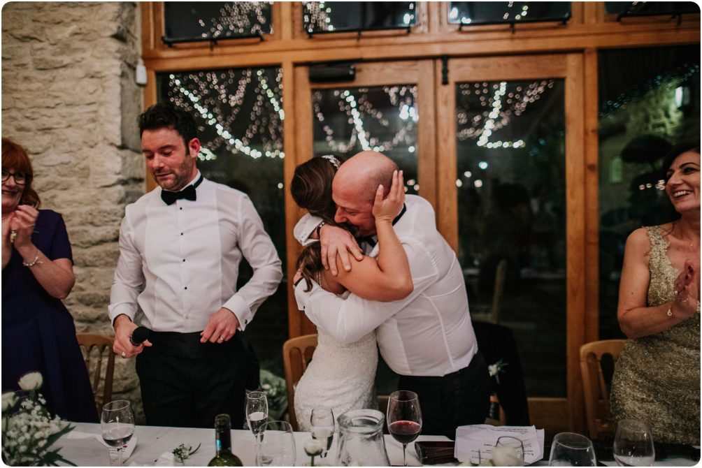 bride hugging her dad after his speech at a kingscote barn wedding