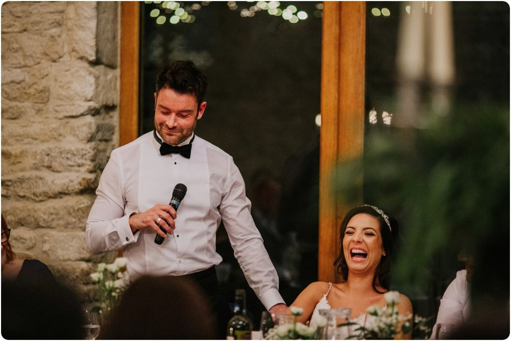 groom making bride laugh at a kingscote barn wedding