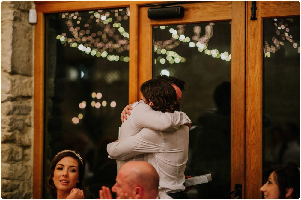 groom and brother of bride hugging during speeches at a kingscote barn wedding