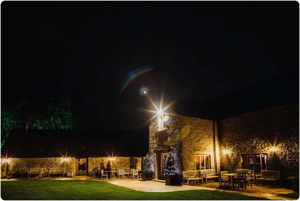 outside of kingscote barn at night at a winter wedding